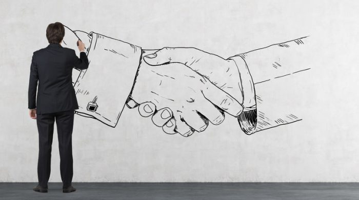 35203402 - businessman in room drawing handshake on wall